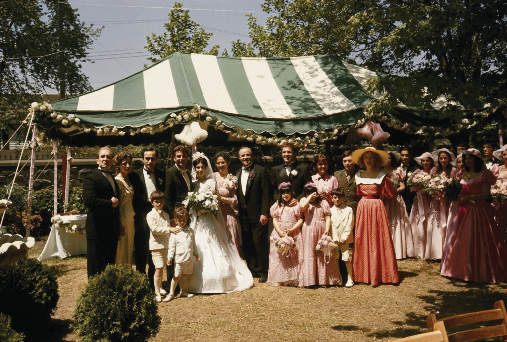 The Corleone family gathers for a family portrait. Daughter Connie wears her wedding dress and smiles happily.