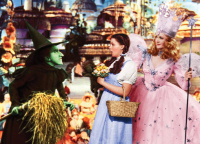 The Wicked Witch leans menacingly towards Dorothy Gale, a girl clad in a blue and white jumper. Dorothy, clutching a bouquet, backs towards Glenda the Good Witch, resplendent in a pink sparkly gown. Munchkins gather in the background.
