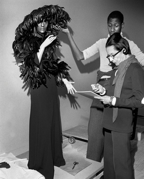 André Leon Talley and Diana Vreeland style a feather headdress onto a mannequin.