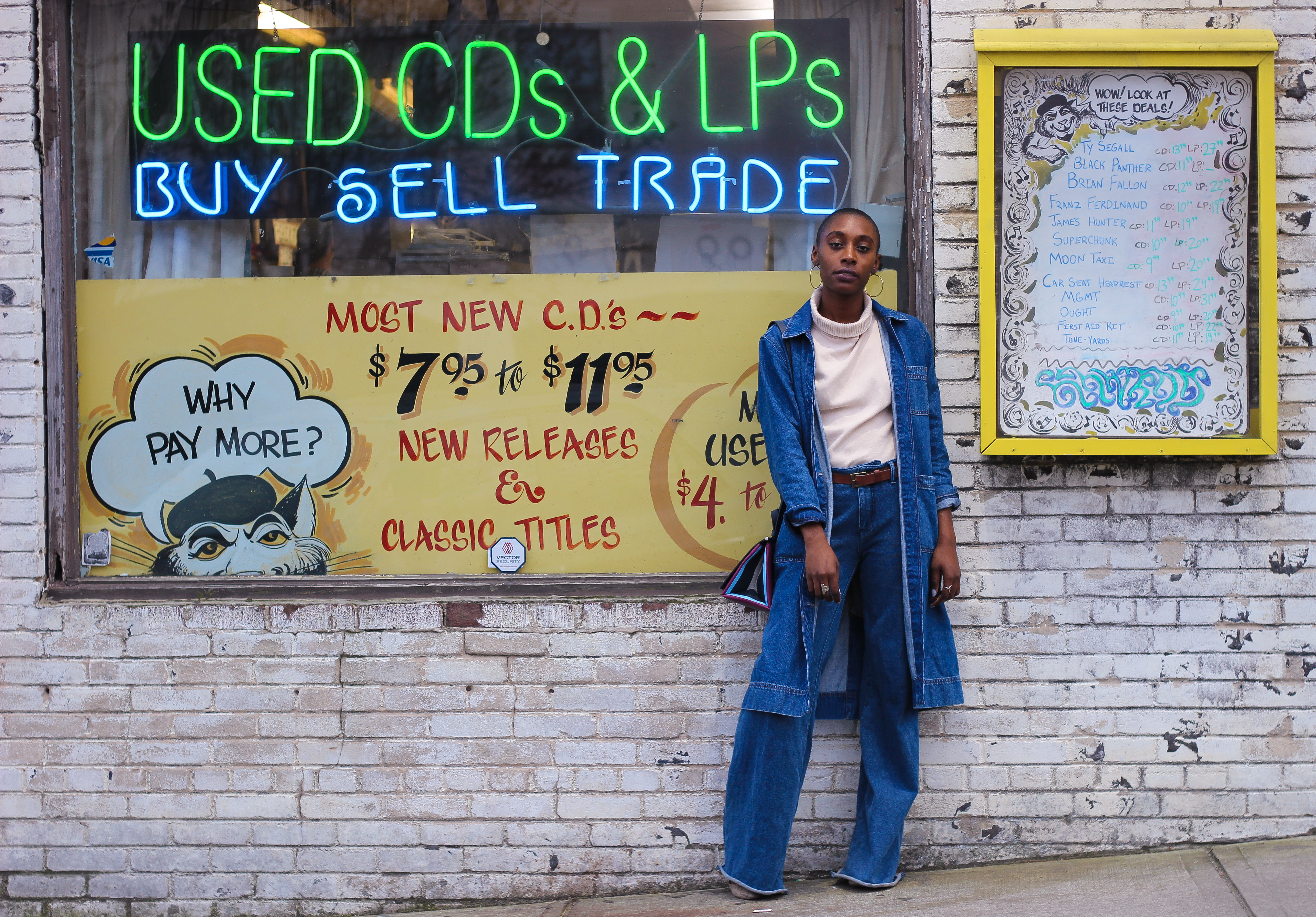 Dani, a local stylist, stands in front of a record store looking very stylish in a denim duster and jeans.