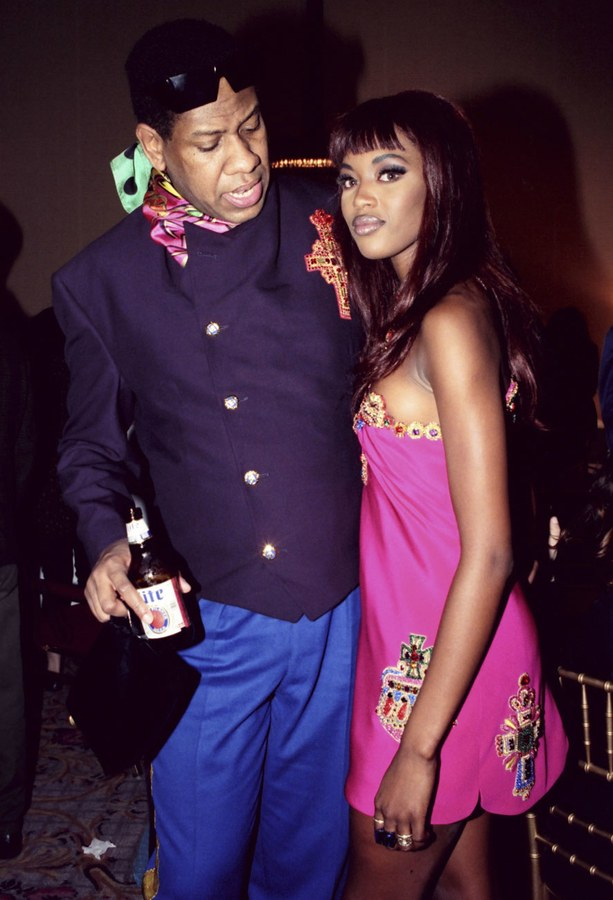 André Leon Talley and Naomi Campbell pose for a picture, he in a blue outfit holding a miller lite, she in a pink minidress.