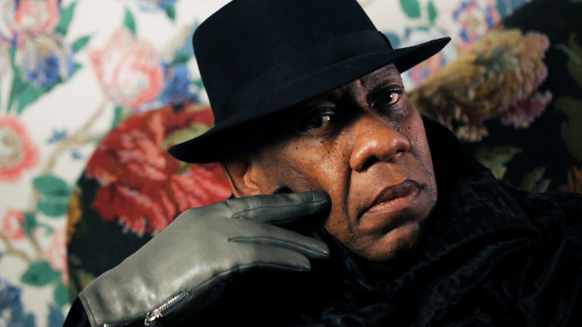 André Leon Talley in a fedora, gazing into the camera. It is a very close portrait and his gray-gloved hand is on his cheek.